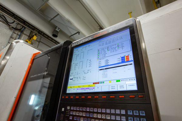 Koneistus. Lähikuvassa moderni koneistamiseen liittyvä laite.